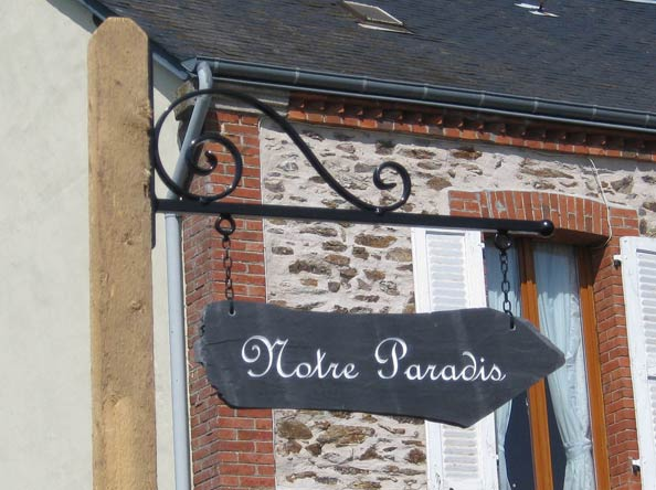 overhead signage with engraved text notre paradis