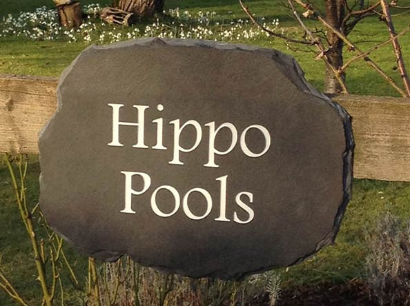 ridged house sign with engraved text hippo pools