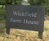 wooden posted business sign for wickfield farm house